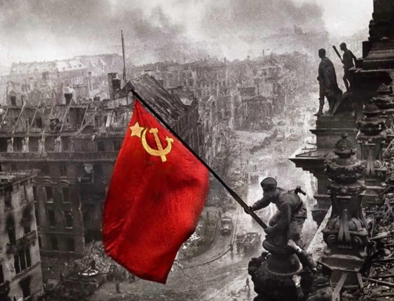 Im Mai 1945 hisst ein Soldat der siegreichen roten Armee die sovietische Flagge auf dem Reichstagsgebäude in Berlin ・ Quelle: Wikimedia ・ Fotograf: Yevgeny Khaldei